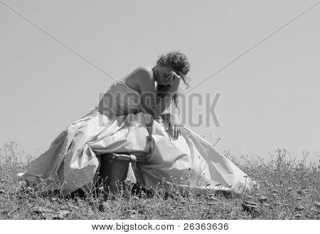 sad abandoned bride sitting on her suitcase