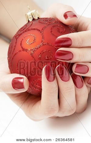hands holding precious red Christmas globe