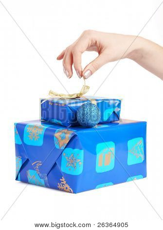 Christmas gifts woman untying a golden bow, blue wrapped boxes