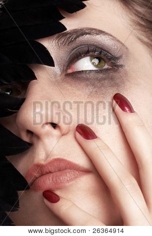 Sad young woman with smeared make-up and black feathered carnival mask