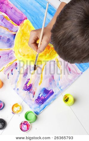 boy painting the sun with fluorescent colors, sunset scene