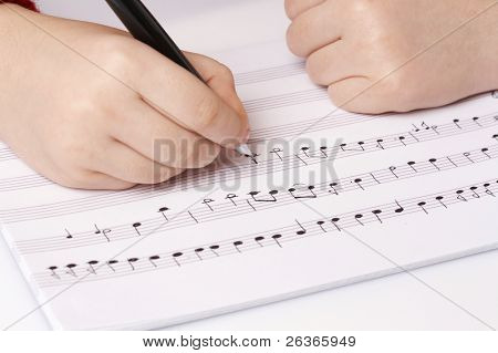 child writing musical notes on school notebook, learning music