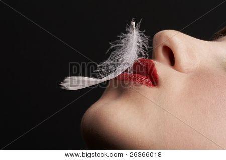 close up of ein Mädchen mit White Feather über ihre Lippen