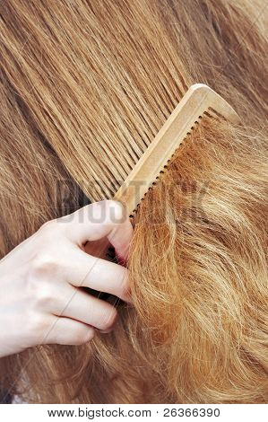 woman combing long blond wavy hair, beauty salon