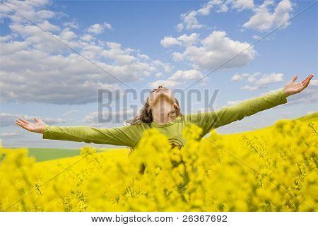 chica extendiendo sus brazos en medio de un campo de colza con azul cielo nublado, libertad al aire libre