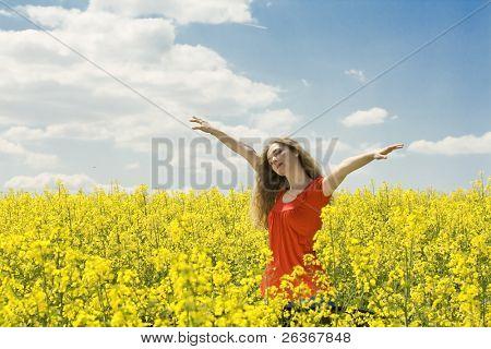 hermosa chica extendiendo sus brazos en medio de un campo de girasol con azul cielo nublado, ' o