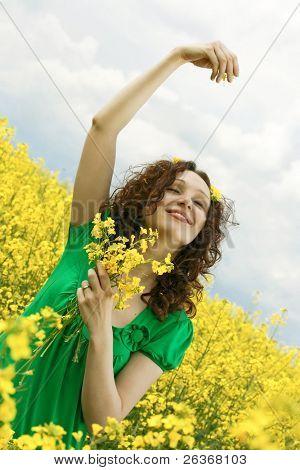 girl having fun in summer rapeseed (canola) field