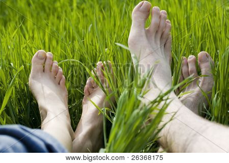 bare feet in green grass, couple relaxing in nature