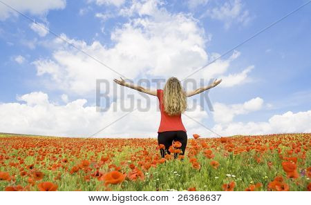 girl spreading her arms in the middle of a poppy field with blue cloudy sky, 'outdoor freedom'