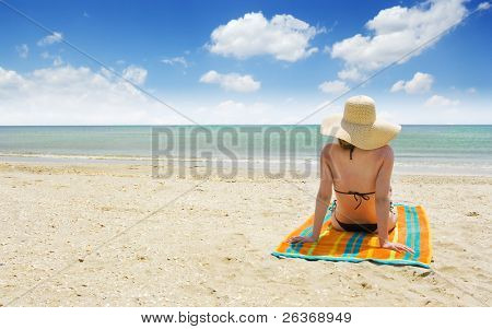 woman relaxing on a beautiful beach against sunny sky