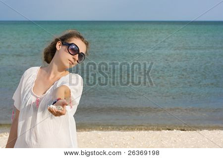 woman holding seashells on a beach in summertime