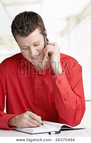 smiling young business man using cellphone and writing in his agenda