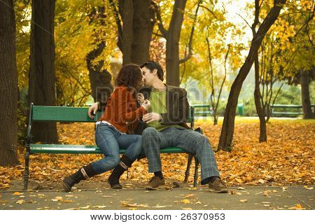 couple kissing on a bench in a park in autumn