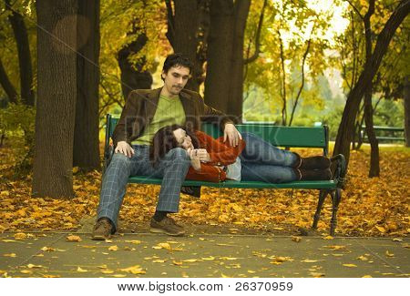 couple relaxing  on a bench in a park in autumn