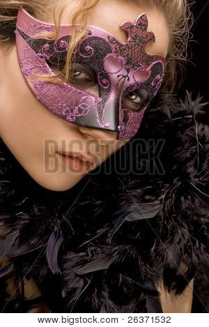 portrait of mysterious blond woman wearing purple stylish carnival mask and black feathers, role play