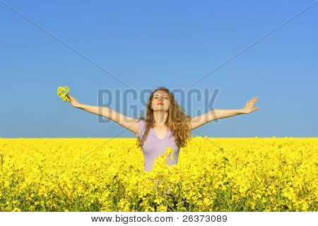 woman in rapeseed (canola) field enjoying the open air