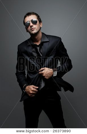 aantrekkelijke jonge man met elegant zwart pak en zonnebril