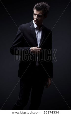 fashion shot of an elegant young man wearing suit