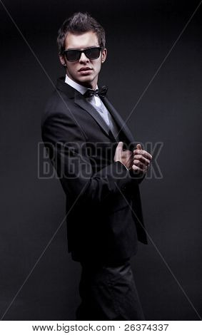 fashion shot of an elegant young man wearing suit, bow tie and sunglasses