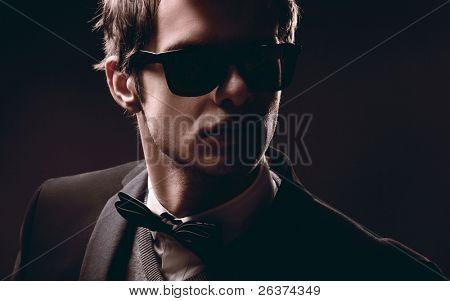 Closeup Retrato de un hombre de moda elegante usar gafas de sol
