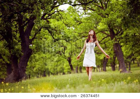 beautiful woman in white walking through the green forest in summer