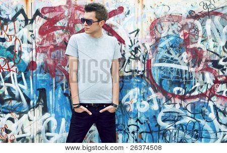 jovem posando em frente a uma parede de grafite colorido