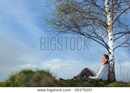 Woman under the birch at field