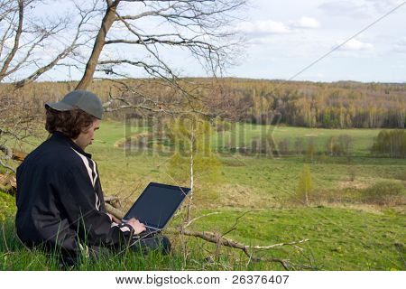 Man with portable computer near small river at nature.