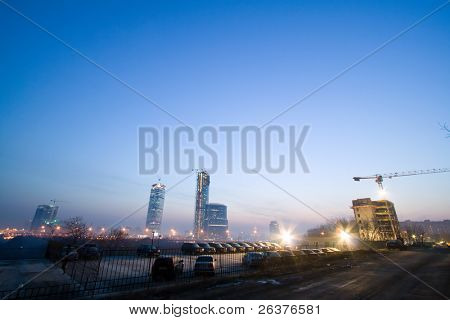 Highrise towers and building under construction at background and parking.