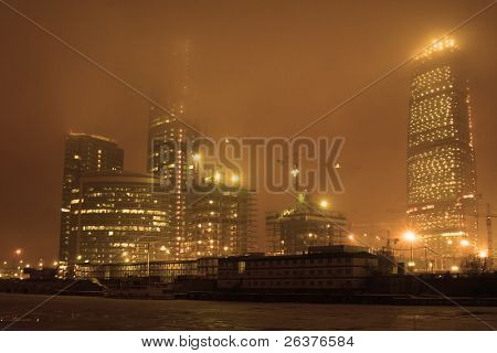 Highrise buildings under construction, river and fog at night city.