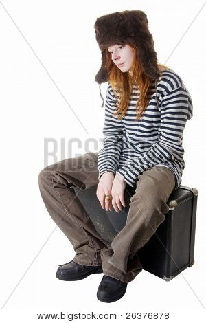 Sad young boyish looking woman in striped vest and cap with ear flaps sitting on old trunk