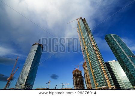 Blue sky with clouds in city and high-rise buildings under construction.