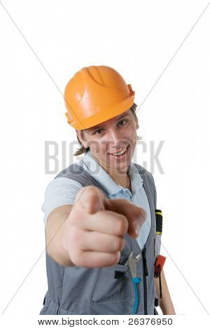 Smiling construction worker pointing by his index finger to you. Isolated with clipping path.
