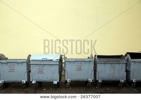 Several metal refuse bins near yellow wall