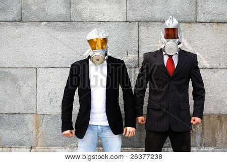 Two businessmen wear gas masks