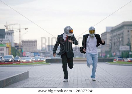 Two businessmen with gas masks running at city