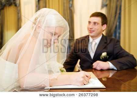 Young couple signing agreement of marriage