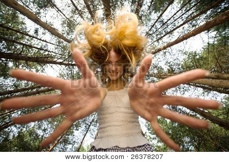 Smiling woman stretch her hands to camera at piny forest