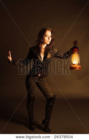 Young woman sneak with old oil lamp. Image with clipping path.