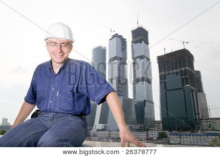 The architect wearing a protective helmet sitting in front of a building site and smiling
