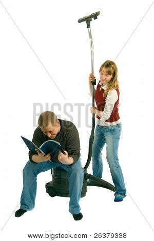 The man is sitting on the vacuum-cleaner and reading a magazine, while the woman is looking over his shoulders at the magazine