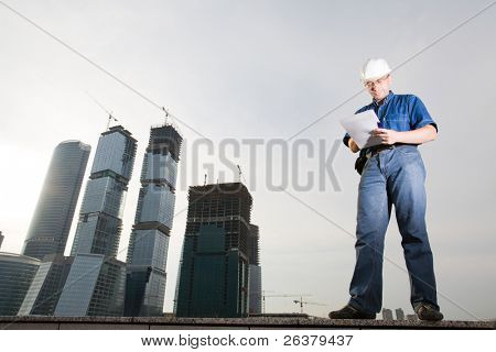 The architect wearing a protective helmet standing in front of a building site and writing something on paper