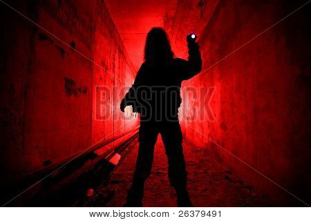 Man with pocket flashlight standing in red tunnel.