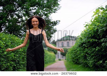 Young beautiful Woman tragen schwarze Kleidung ist zu Fuß mit Armen weit geöffnet durch den Park in der Nähe von das
