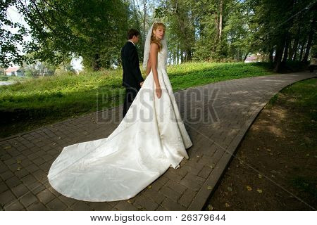 A bride and a groom are walking together along the path, the bride is turning towards us.