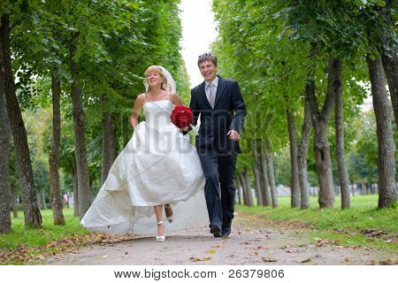 Just married couple is walking fast down the path in the park. They are laughing and the bride is raising a little her gown