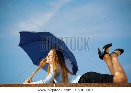 One young beautiful woman enjoys the sunshine on the cloudy sky lying under the umbrella.