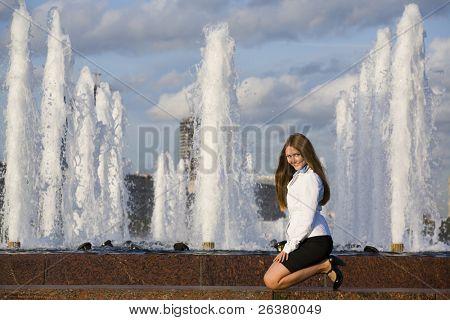 Um jovem bonito está sentado sobre os joelhos perto da fonte do Parque, voltando-se para a câmera para