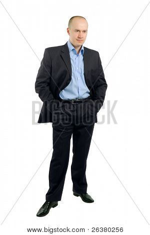 full length portrait of a businessman who is standing and holding his hands in pockets
