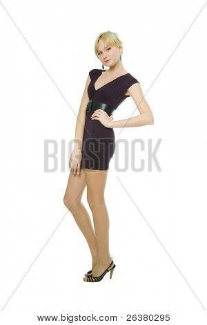 One young beautiful  blond woman wearing short violet dress is standing on the white isolated background.